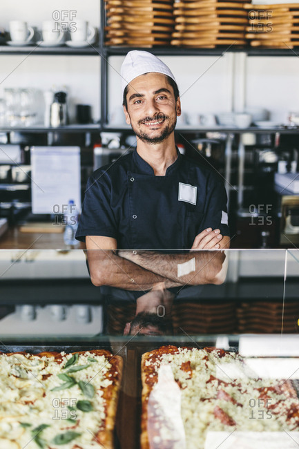 Portrait of confident smiling chef with arms crossed standing in pizzeria