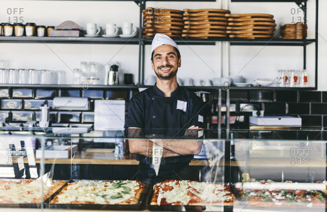 Portrait of smiling chef with arms crossed standing by retail display in pizzeria