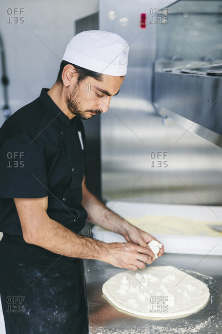 Chef putting cheese on pizza dough in commercial kitchen at pizzeria