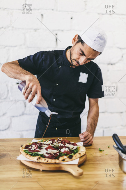 Chef pouring sauce on pizza in commercial kitchen