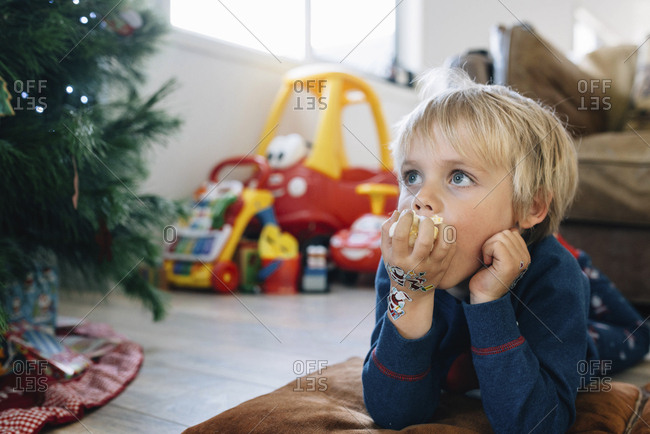 Boy eating popcorn while watching TV at home