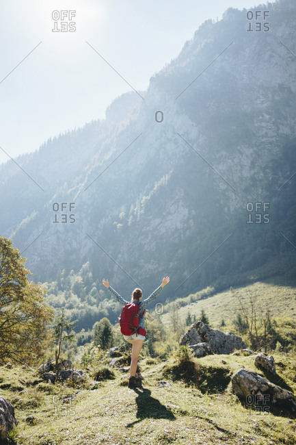 Rear view of backpacker with arms raised standing on field by mountain during sunny day