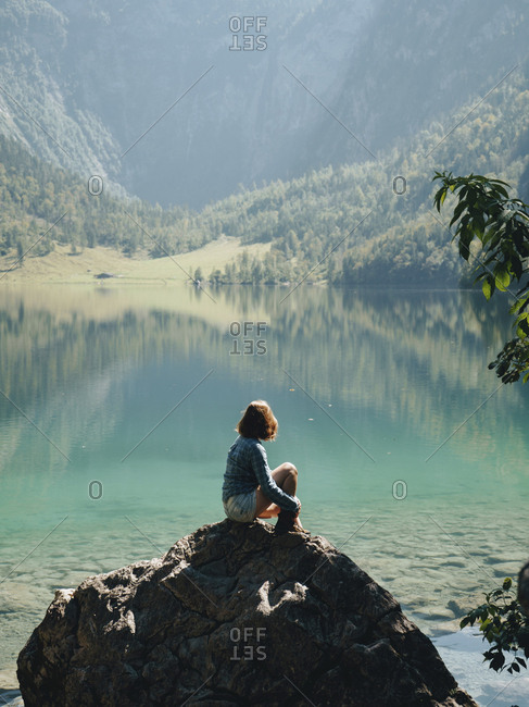 Side view of female tourist looking at lake while sitting on rock against mountains during sunny day