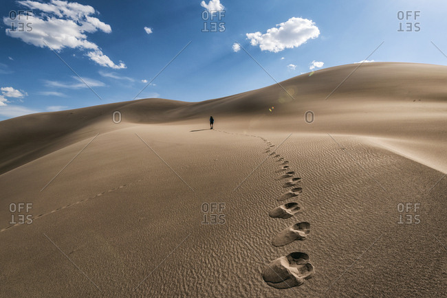 Mid distance view of hiker walking on desert against sky at Great Sand Dunes National Park during sunny day