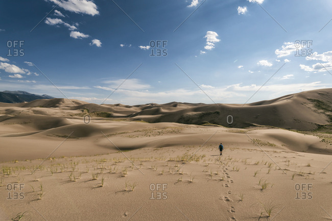 Mid distance view of hiker walking on desert against sky at Great Sand Dunes National Park