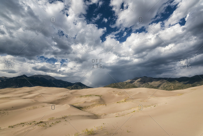 Scenic view of desert against cloudy sky at Great Sand Dunes National Park