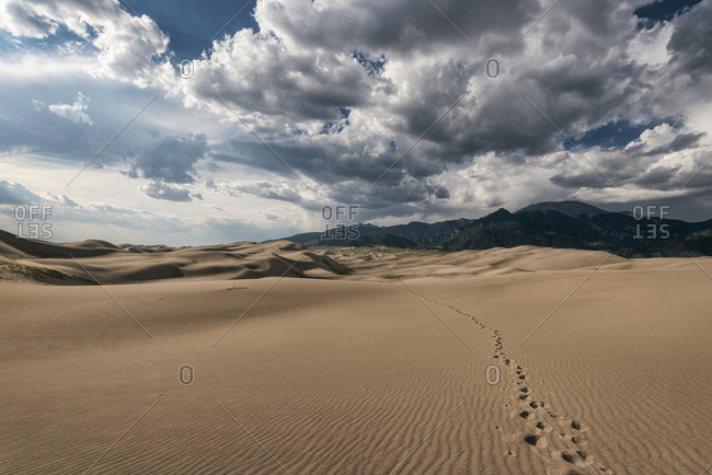 Scenic view of sand dunes and mountains on desert against cloudy sky at National Park