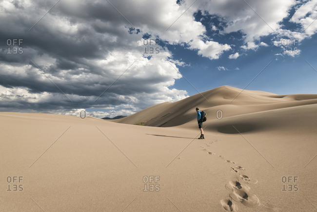 Side view of hiker standing on desert against cloudy sky at Great Sand Dunes National Park