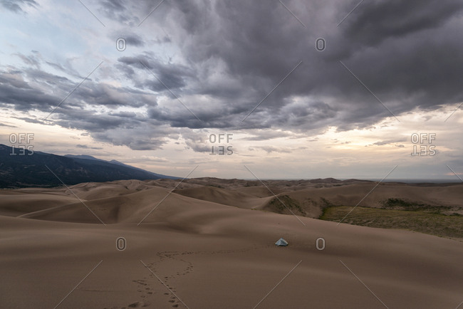 Scenic view of desert against cloudy sky at Great Sand Dunes National Park during sunset