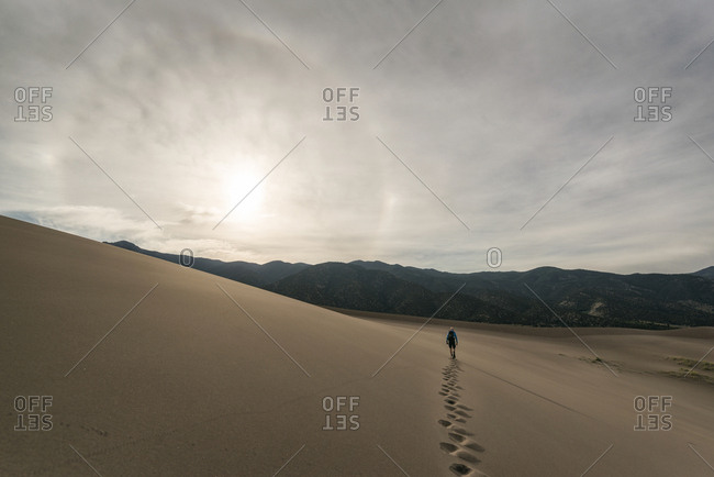 Rear view of hiker walking on desert against sky at Great Sand Dunes National Park during sunset
