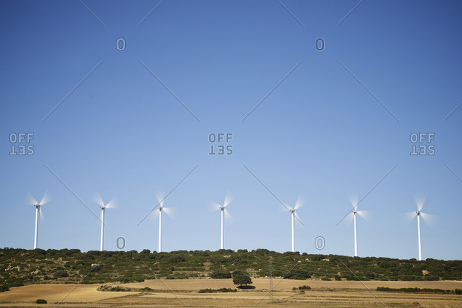Windmills spinning against clear blue sky