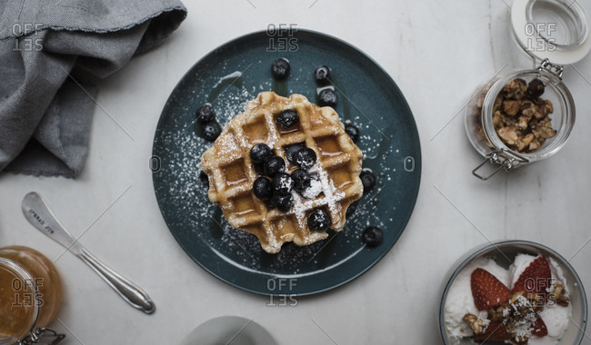 Overhead view of blueberries on waffles in plate