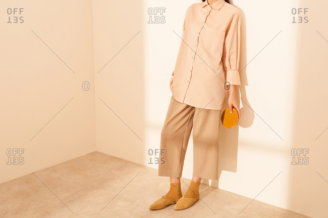 Model leaning against a wall, wearing beige clothes