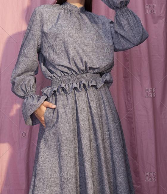 Model wearing dress against pink background