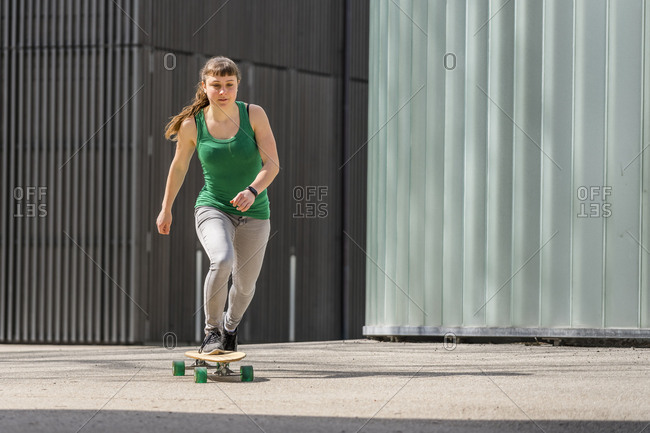 Teen with longboard, 18 years old, female, urban environment
