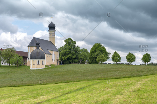 Wilparting Pilgrimage Church with green meadows and trees on a sunny day in springtime, Irschenberg, Upper Bavaria, Germany
