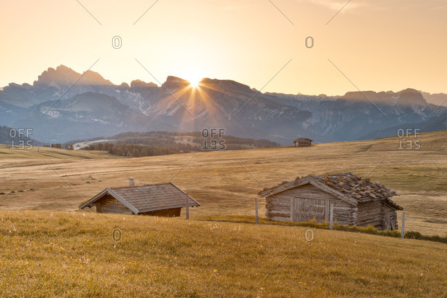 Europe, Italy, Bolzano, South Tyrol, Alpe di Siusi - Seiser Alm, Dolomites, the sun rises behind the Sassolungo Langkofel, in the foreground some wooden huts
