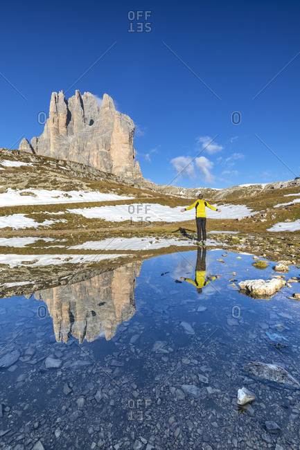 observing the Tre Cime di Lavaredo  /  Drei Zinnen reflected in a mirror of water towards the lavaredo fork, Auronzo di Cadore, Belluno, Veneto, Italy