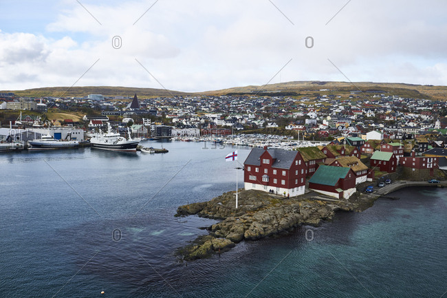 Faroe Islands, View of little Harbor Town, snowcapped mountain in the background
