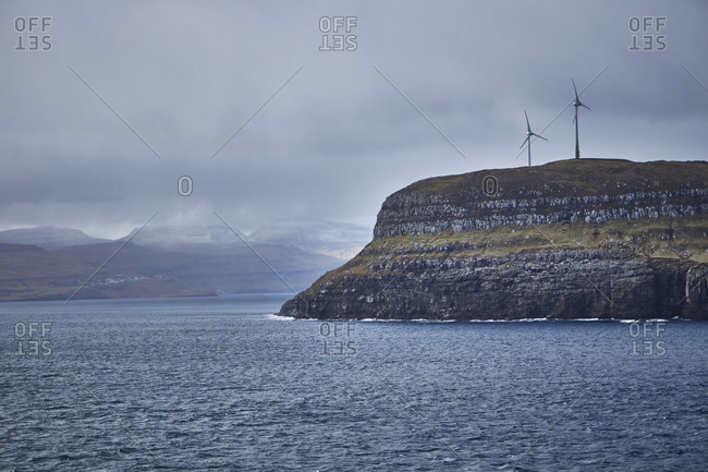 Iceland, east Fjords in the arctic ocean, cloudy sky and two windmills