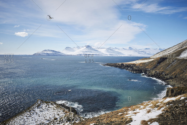 Iceland, view of the east Fjords, snowy mountains in the distance, blue sky