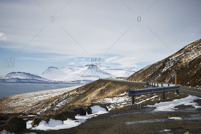 Iceland, windy road through the east Fjords, cloudy sky and snowcapped mountains in the distance