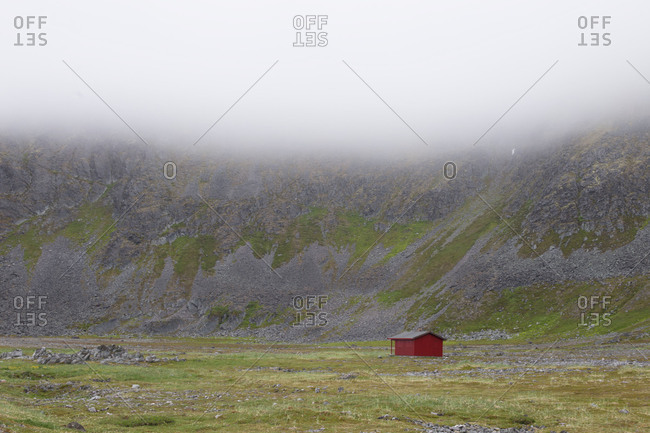 Red cottage in a foggy landscape, Berlevag-Kongsfjord, North Norway
