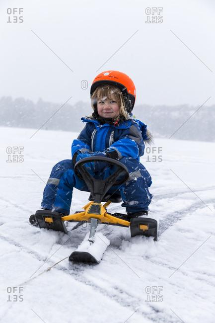 Boy on small snowmobile