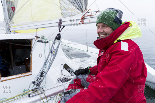 Smiling man on yacht on snowy day