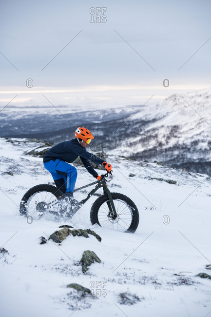 Man cycling in winter landscape