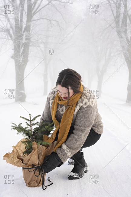 Woman with potted pine tree