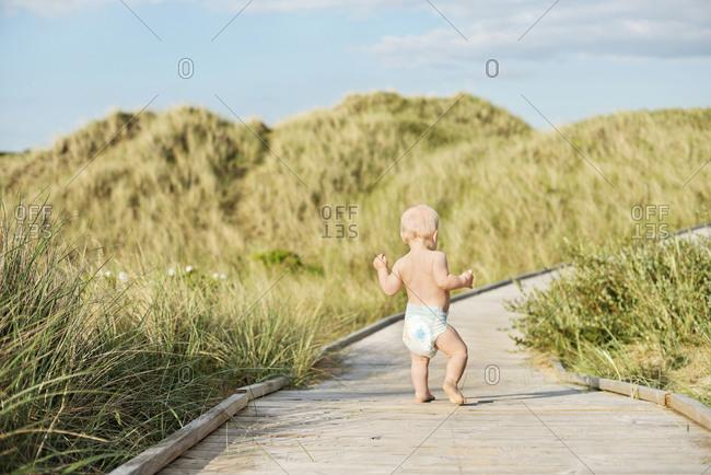 Toddler walking on boardwalk - Offset