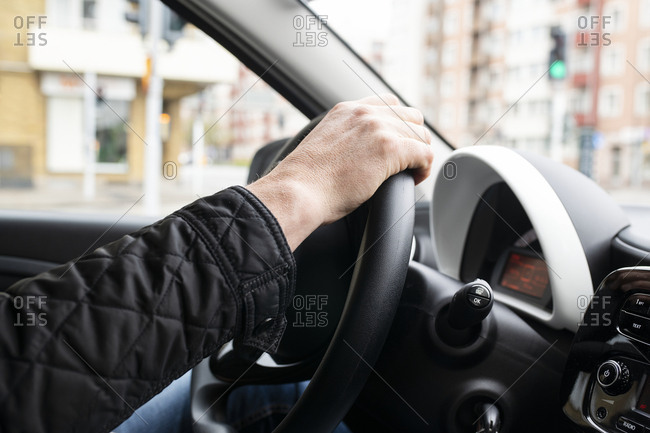 Mans hand on steering wheel inside car.
