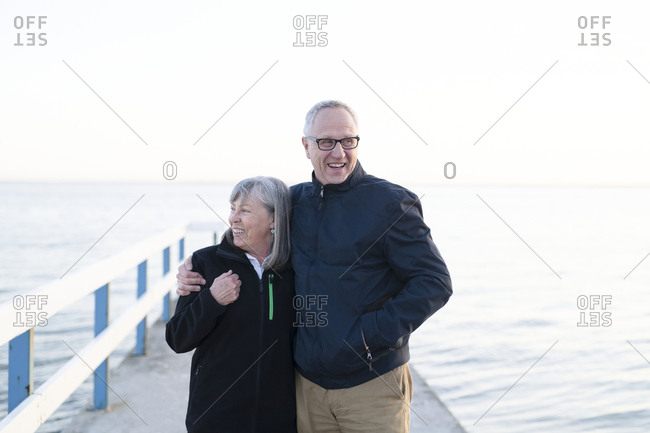 Older couple hugging on a dock