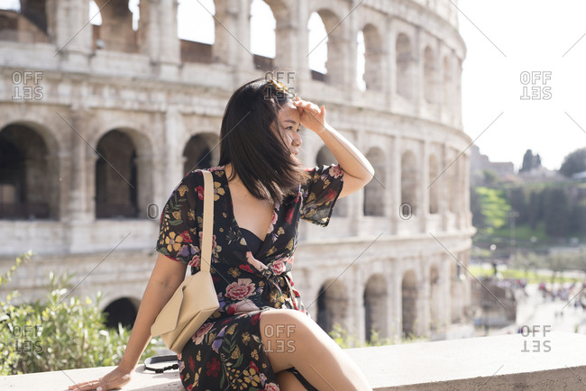 Woman sitting on ledge in rome