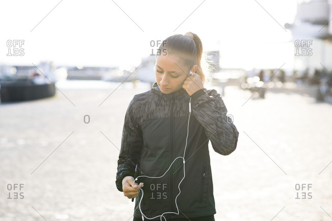 Woman preparing for a run by putting in headphones