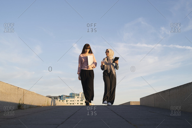 Two woman walking and talking on a sidewalk