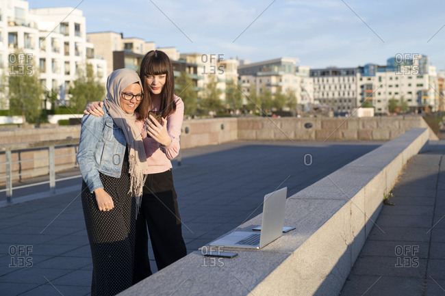 Two woman looking at a phone outdoors with a computer setup on a ledge
