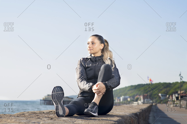 Woman sitting on a ledge with one knee up