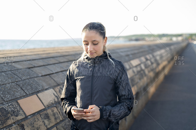 Woman holding and looking at a phone outdoors