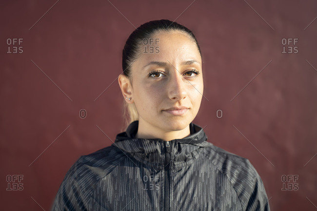 Portrait of a woman with a red wall in the background
