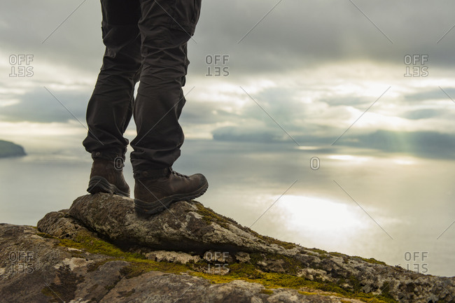 Hiker standing on rocks, low section