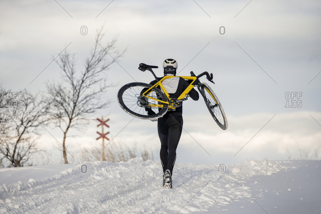 Man carrying bicycle at winter