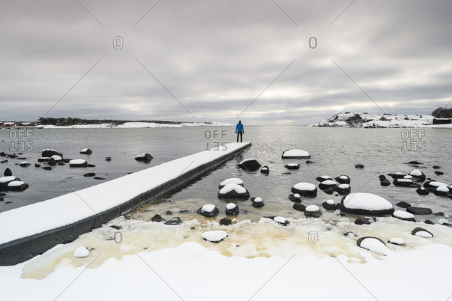 Man standing on jetty in winter