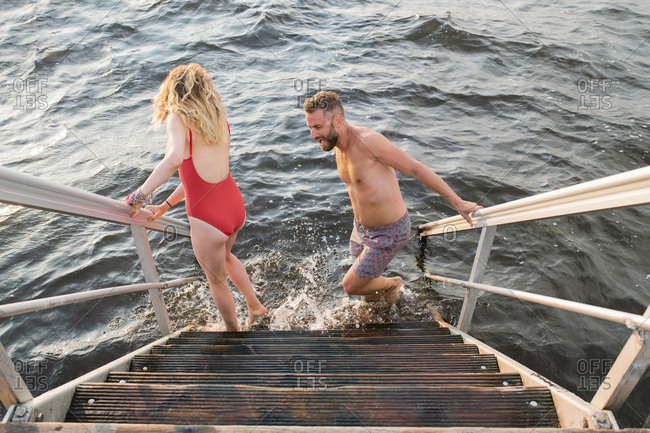 Two people jumping into water from stairs