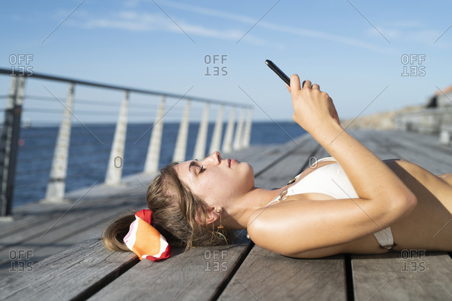 Woman laying on beach boardwalk looking at phone