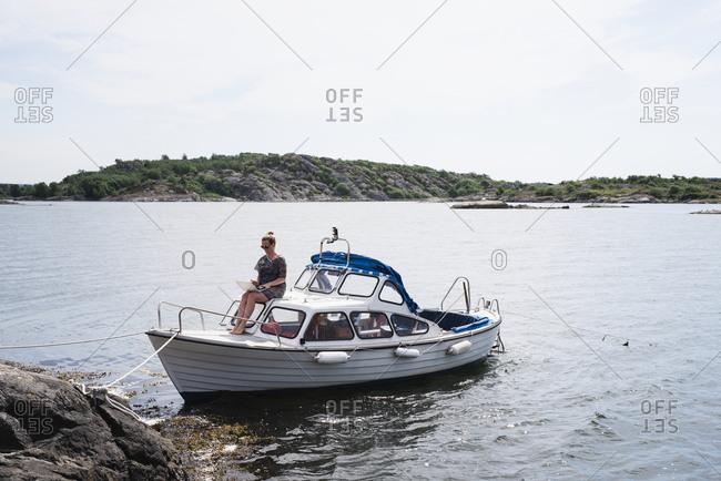 Woman using laptop on motorboat