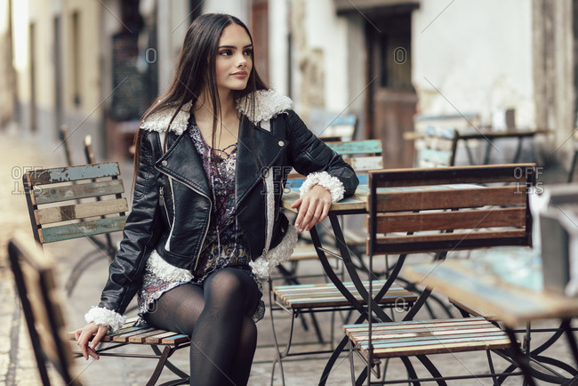 Young beautiful girl wearing modern outfit sitting  on the outside terrace of a charming bar. Lifestyle and fashion concept.
