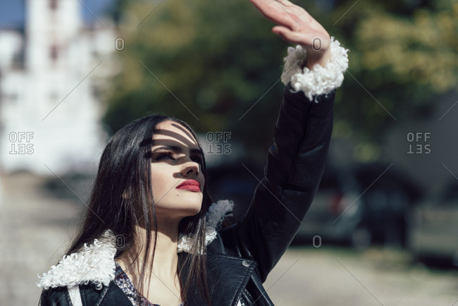 Young beautiful girl making shadow on her face with her hand outdoors. Lifestyle concept.