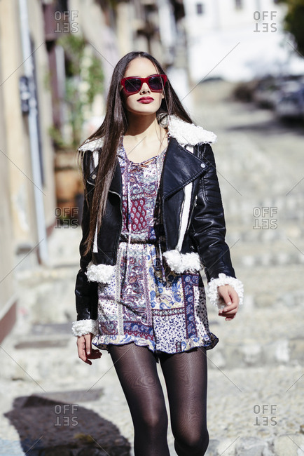 Young beautiful girl wearing modern outfit with purple sunglasses outdoors. Lifestyle and fashion concept.